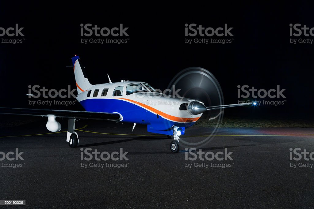 The small single-engine piston aircraft on the runway, illuminated with propeller stock photo