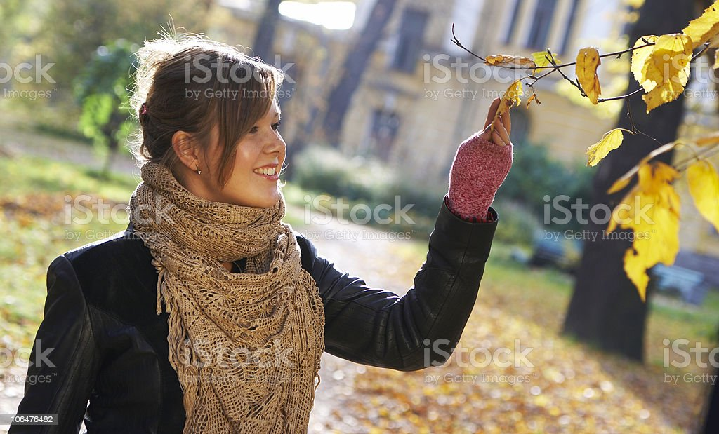 The smiling girl considers autumn leaves royalty-free stock photo