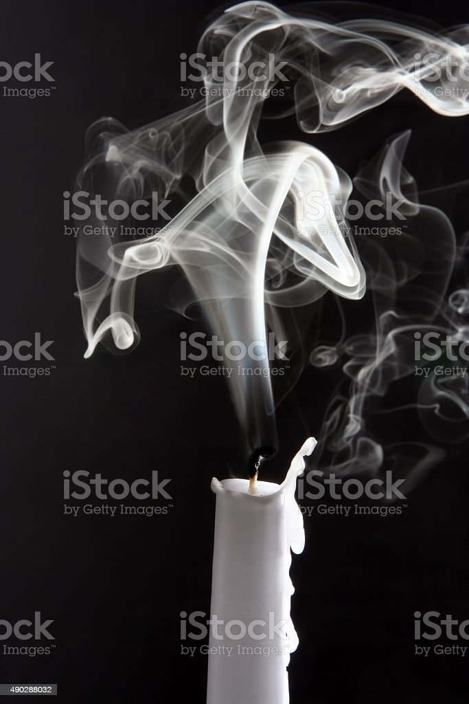 the smoke of an extinguished candle on black background stock photo