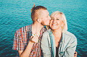 The son kisses and hugs his mom in summer day