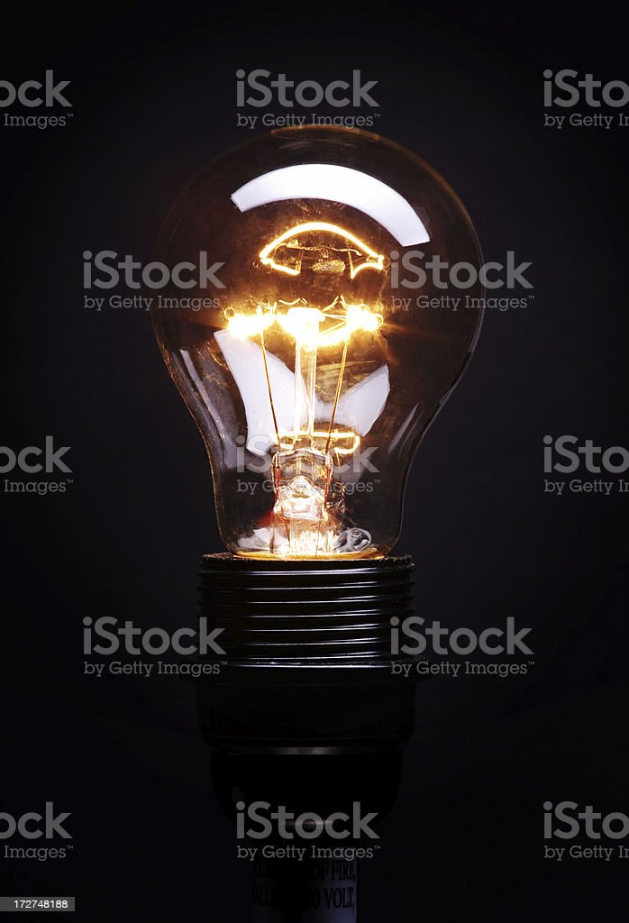 The sparks of a lit light bulb over a black background stock photo