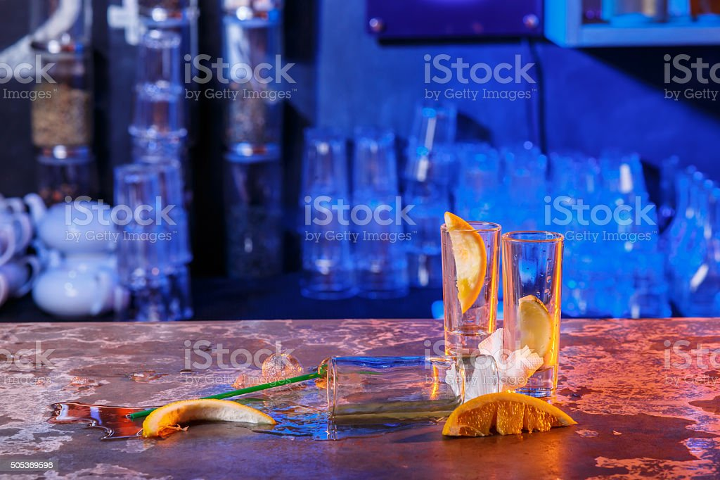 The spilled cocktails with ice cubes on blue color in stock photo