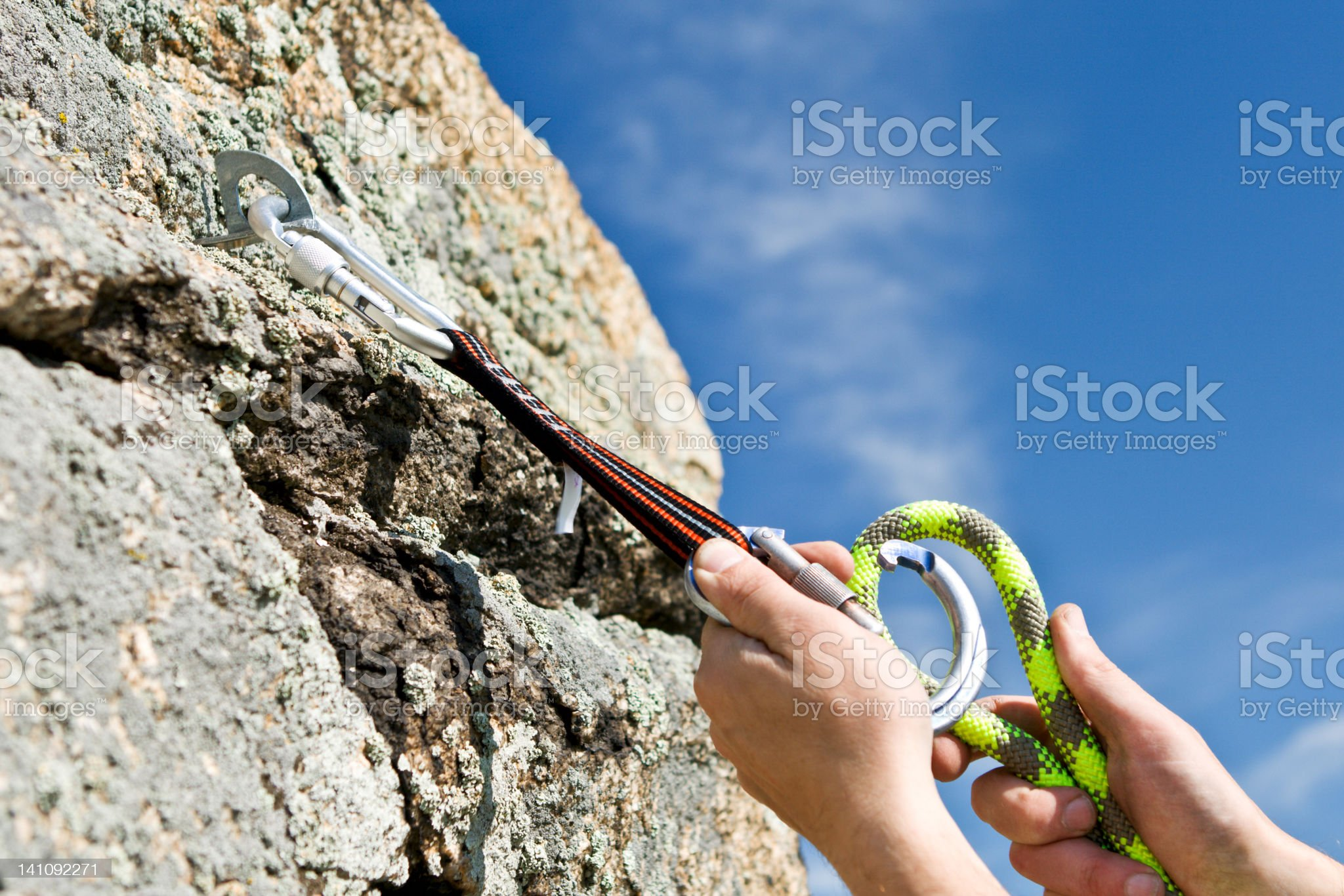 The sportsman hangs up carbine and guy-rope in rock royalty-free stock photo
