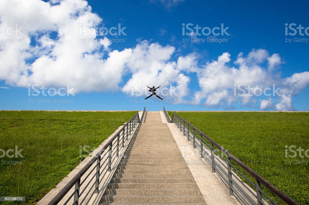 The stairs to the success.happy businessman  jumping over the top stock photo