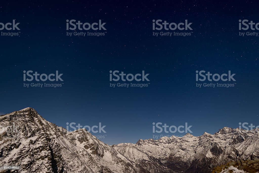 The starry sky above the Alps in winter under moonlight stock photo