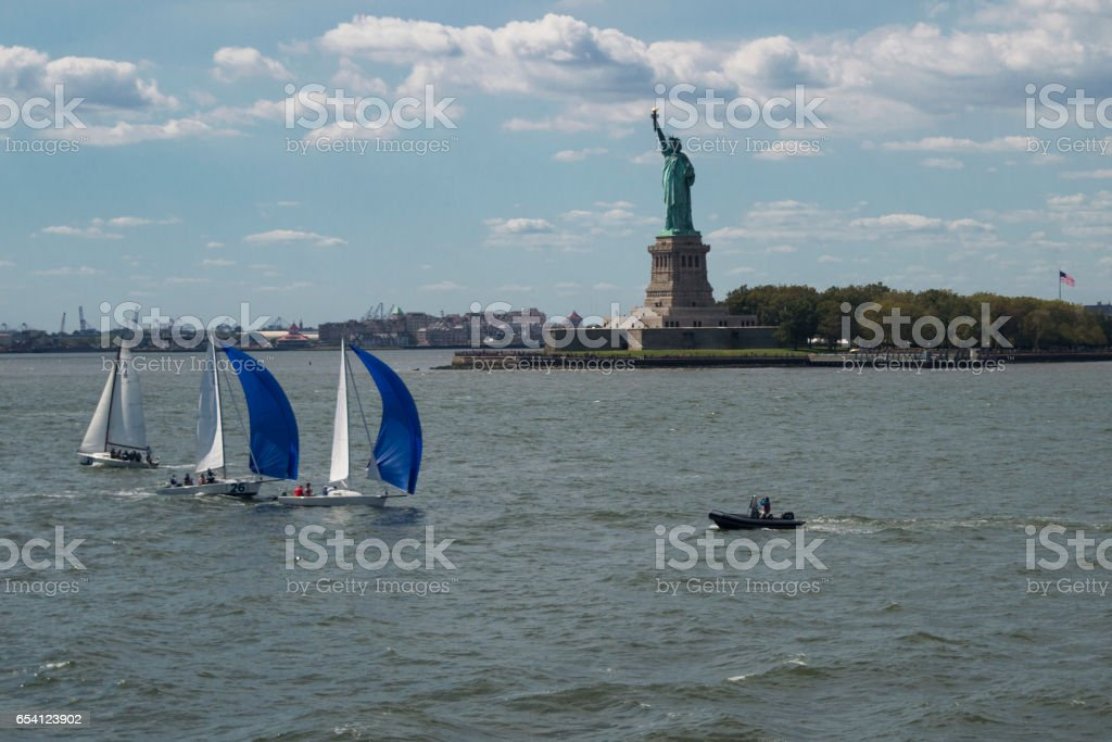 The Statue of Liberity New York City lower Manhattan financial wall street district buildings skyline on a beautiful summer day with blue sky stock photo