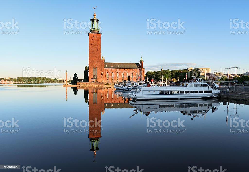The Stockholm Stadshuset in early morning light reflected in water. stock photo
