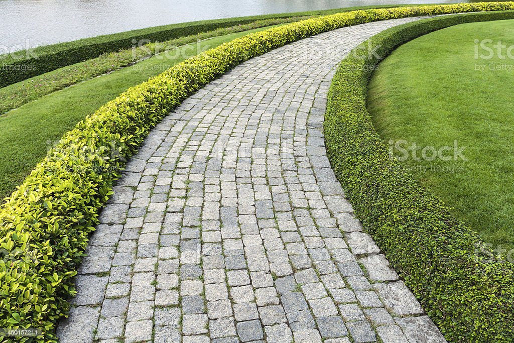 The Stone block walk path with green grass stock photo