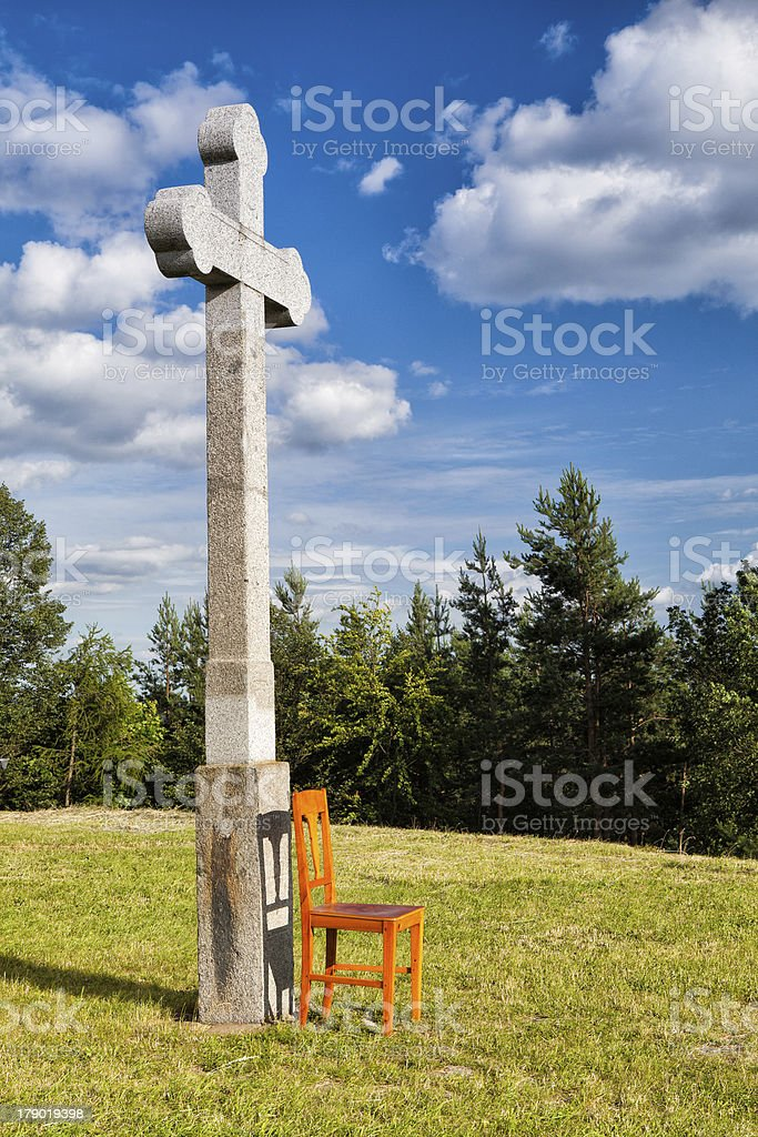 The stone cross and empty wooden chair royalty-free stock photo