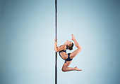 The strong and graceful young girl performing acrobatic exercises on