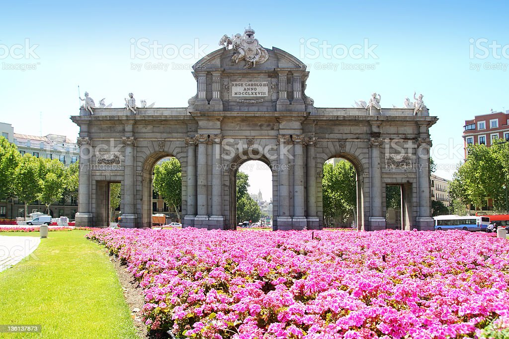 The stunning Madrid Puerta de Alcala with flower gardens stock photo