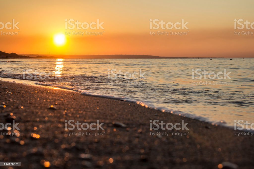 The sun comes from the Italian sea coast stock photo