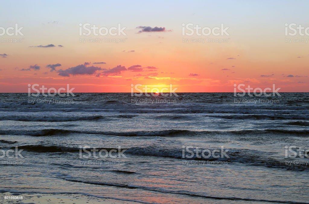 The sun rising over the ocean stock photo
