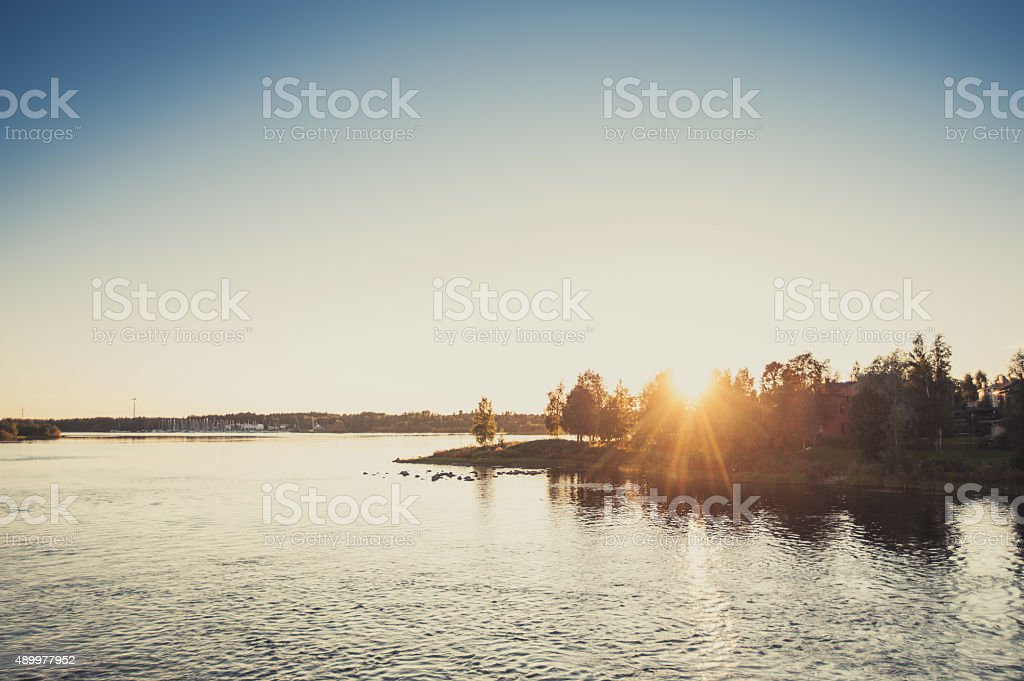 The sun sets behind an island in the sea stock photo
