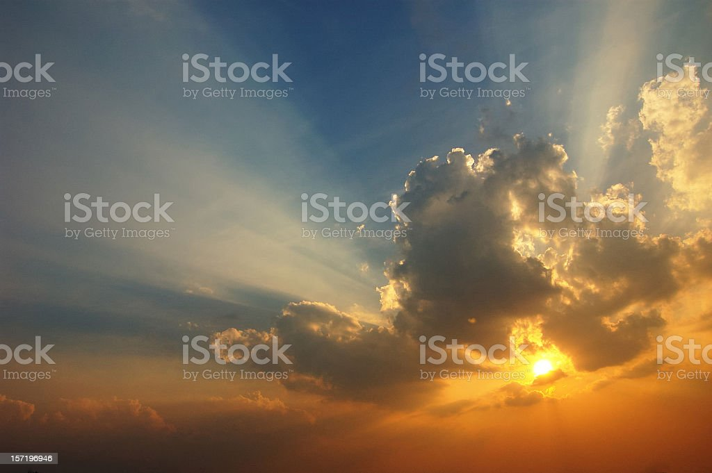The sun setting with clouds forming around it royalty-free stock photo