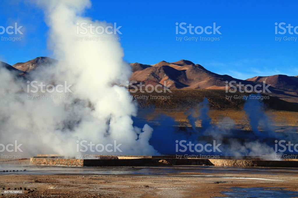 the sunlight let the steam of the geysers of el tatio shine stock photo