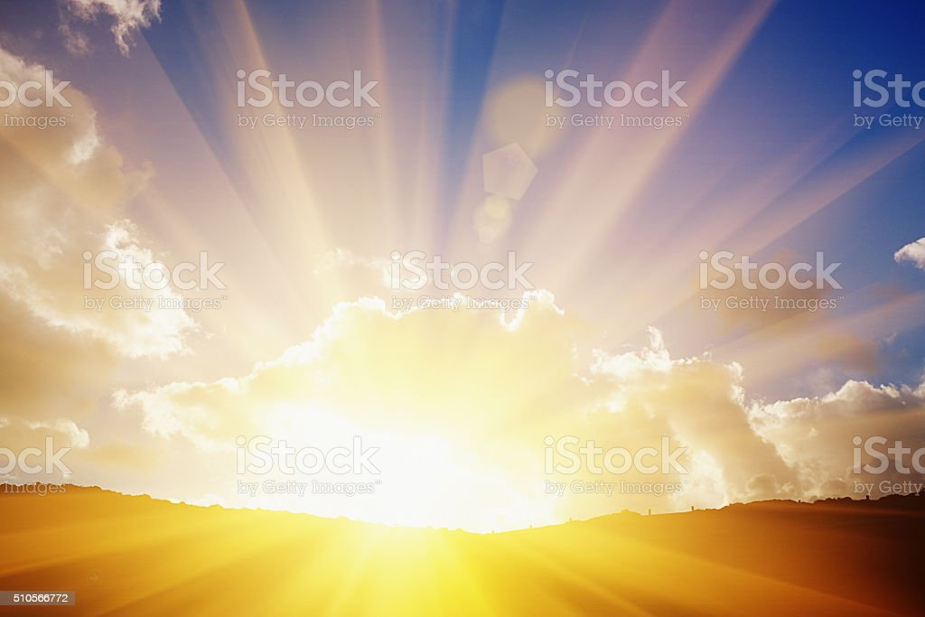 The sun's rays on the horizon flare dramatically through clouds stock photo