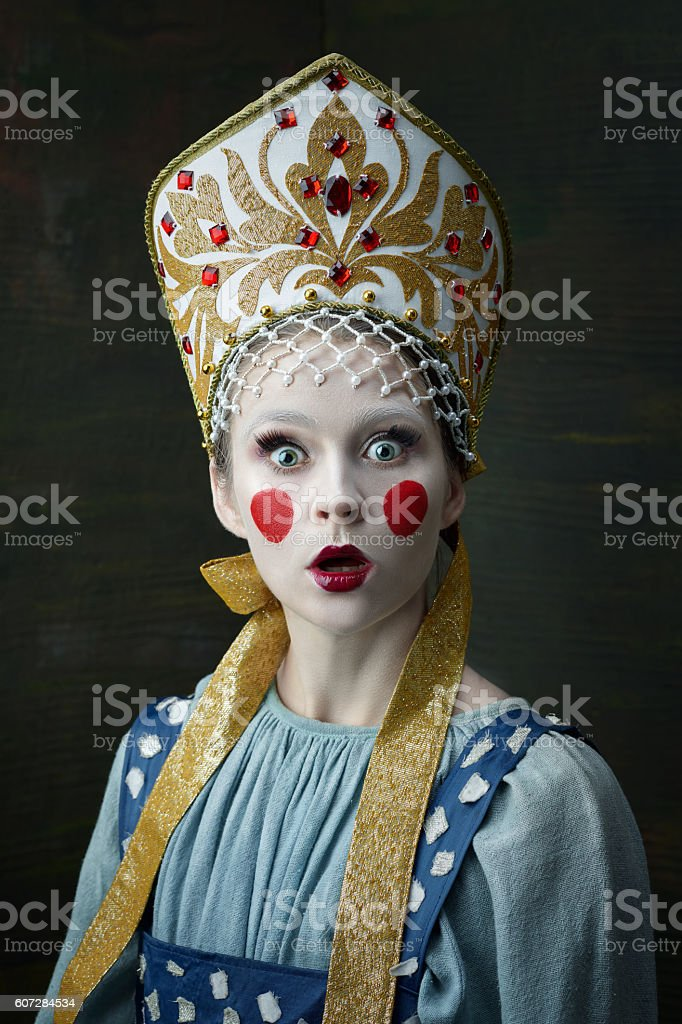 The surprised girl posing in Russian traditional costume. stock photo