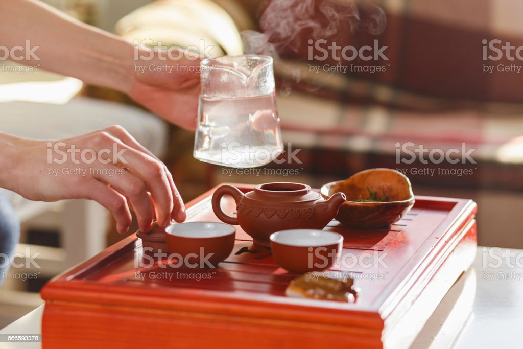 The tea ceremony. The woman pours hot water into the teapot stock photo