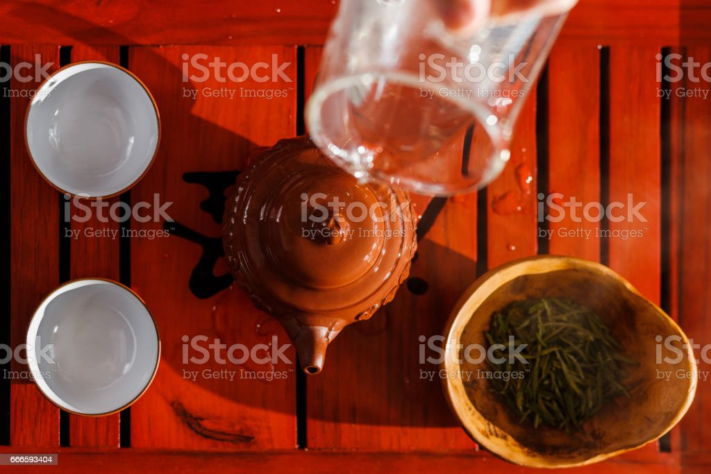 The tea ceremony. The woman rinses the teapot stock photo