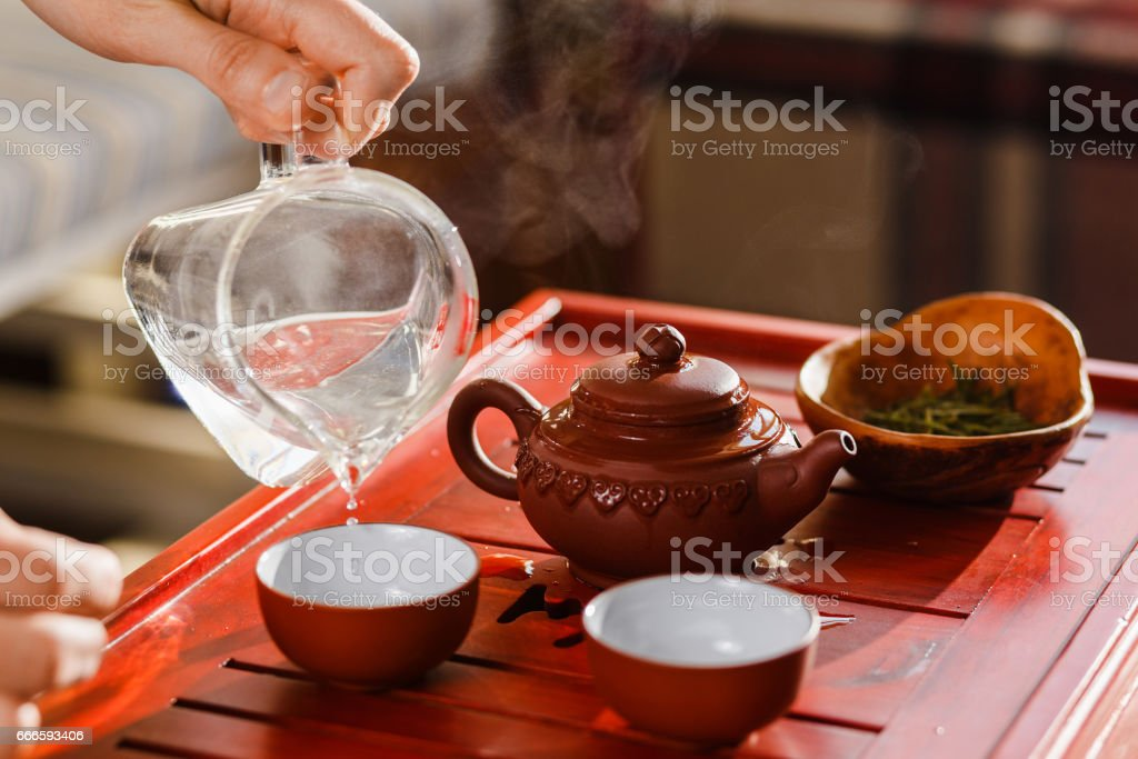 The tea ceremony. Woman pours tea in a tea bowl. stock photo