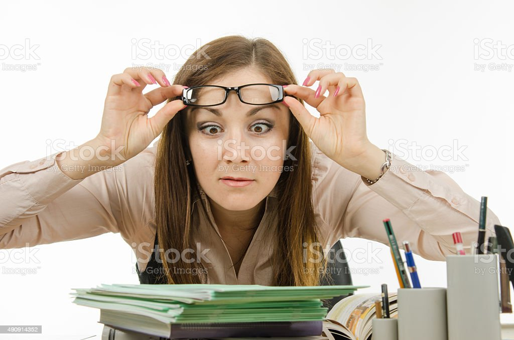 The teacher stares at the pile of notebooks stock photo