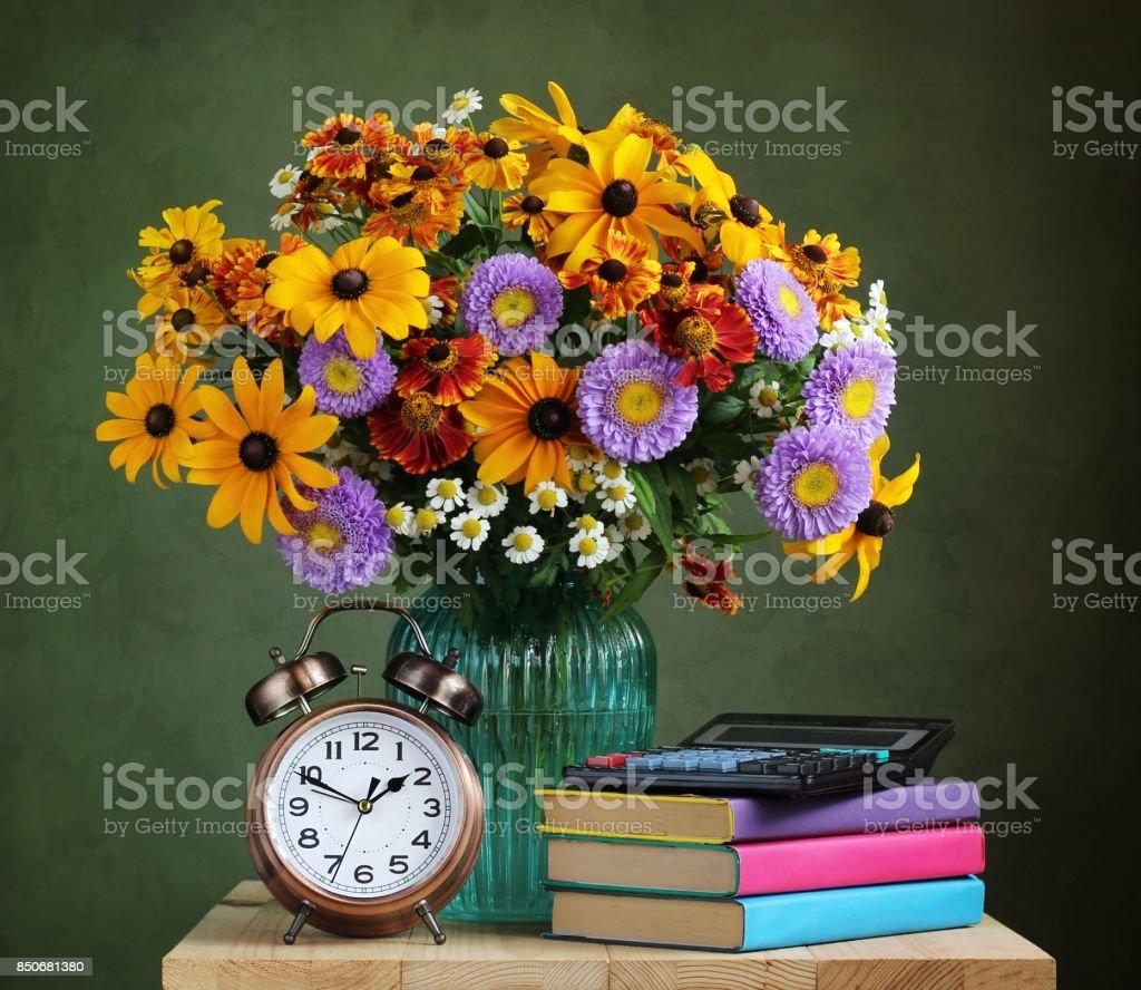 The teacher's day. Autumn bouquet and textbooks. stock photo
