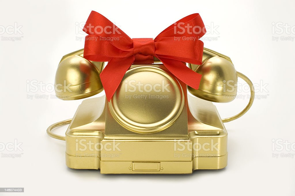 The telephone of gold colour with a red tape. royalty-free stock photo