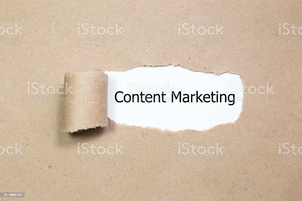 The text Content Marketing appearing behind torn paper. stock photo