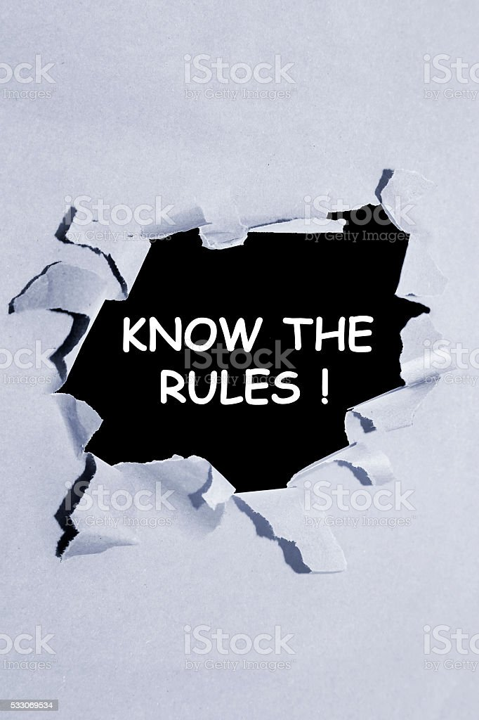 The text KNOW THE RULES! behind torn paper stock photo