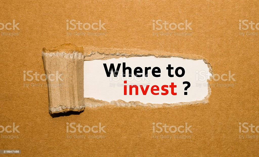 The text Where to invest appearing behind torn brown paper stock photo