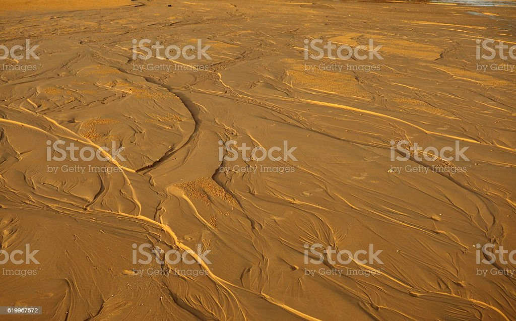 The texture of wet sea sand with patterns  water stock photo