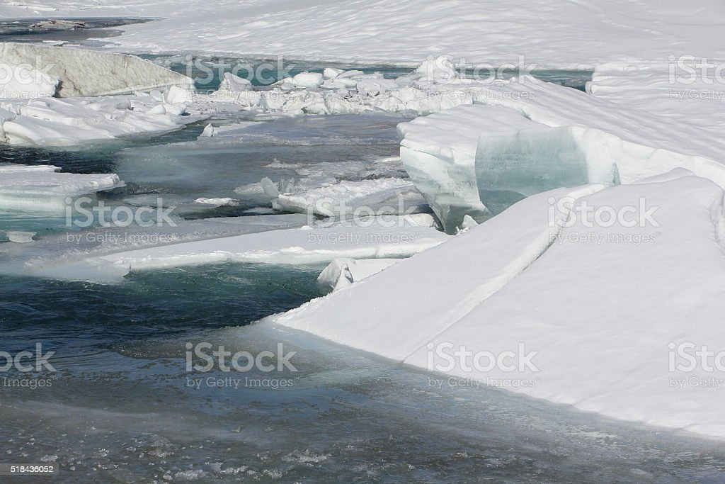 The thawing ice on the mountain river in the spring stock photo