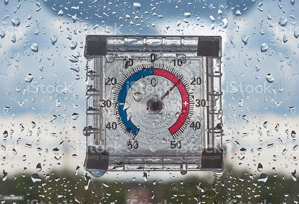 The thermometer on the  of the window, the rain poured .. stock photo