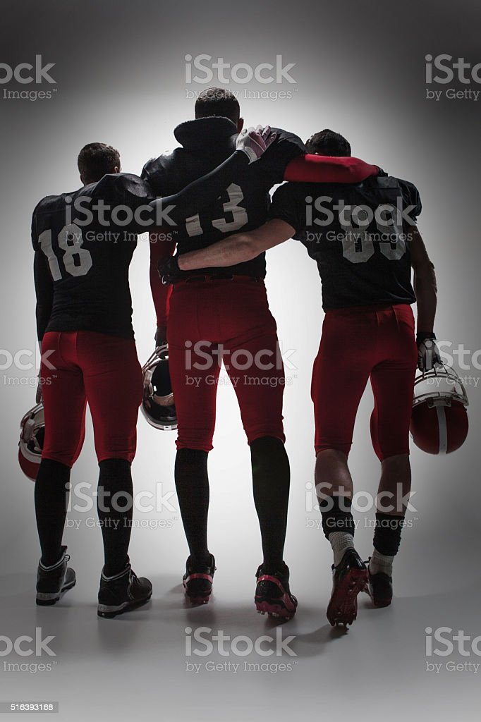 The three american football players on gray background stock photo