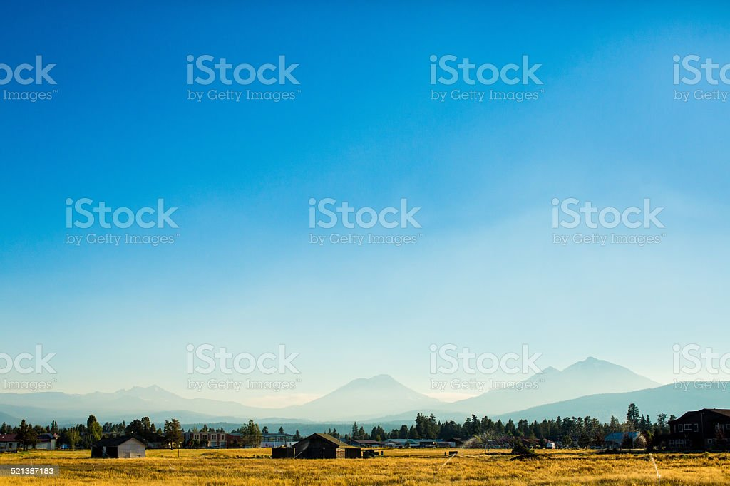 The Three Sisters Mountains rise over Sisters, Oregon stock photo