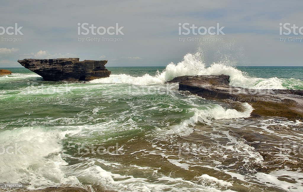 The tide waves splash over rocks stock photo