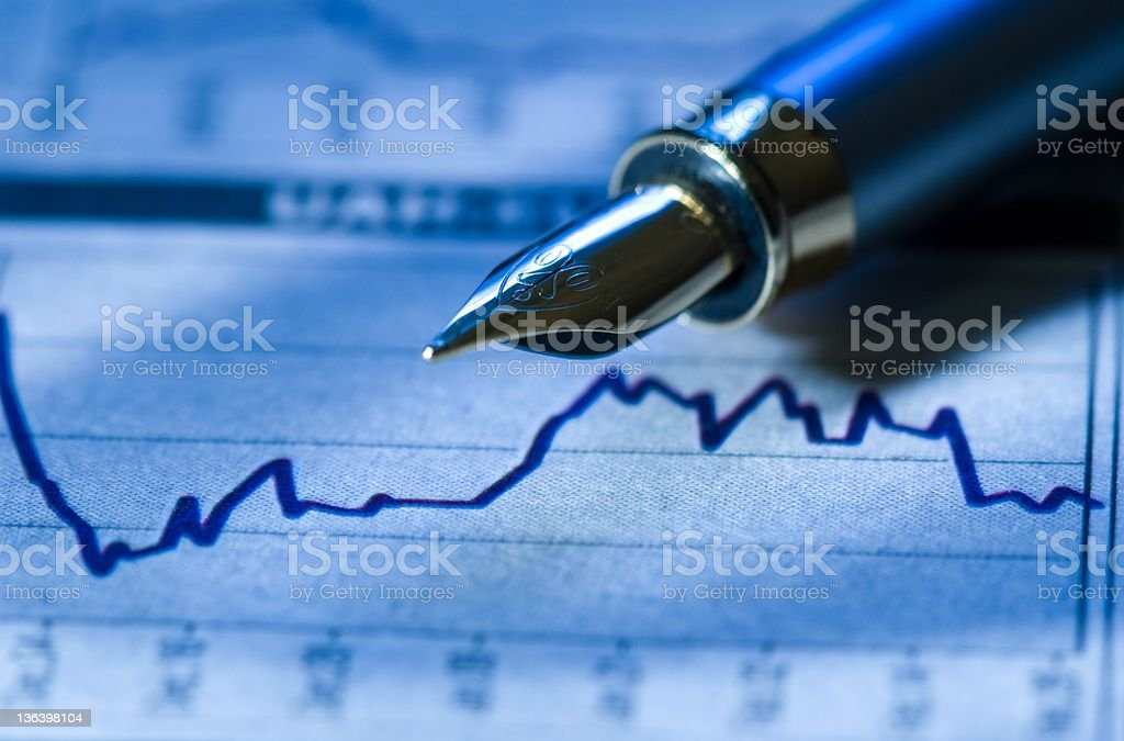 The tip of a fountain pen and a financial graph royalty-free stock photo