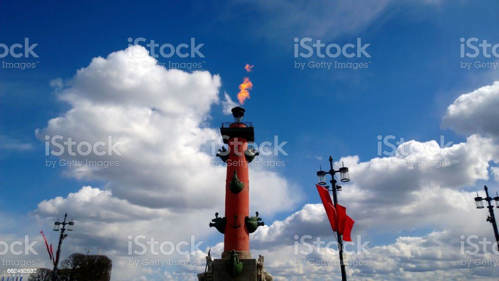 The torch with fire on the Rostral column in St. Petersburg during the celebration of Victory Day. Beautiful cloudy sky stock photo