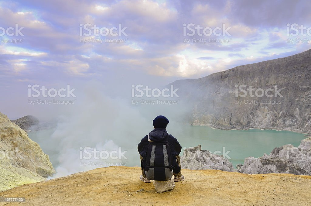 The Tourist relaxing on a rock at Kawah Ijen Volcano royalty-free stock photo