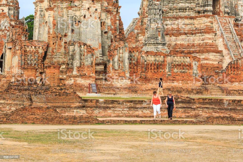 AYUTTHAYA,  THAILAND - MARCH 25, 2017 : The tourists  visiting ruin brick temple of Wat Chaiwattanaram  in Ayutthaya Historical Park, Thailand. stock photo