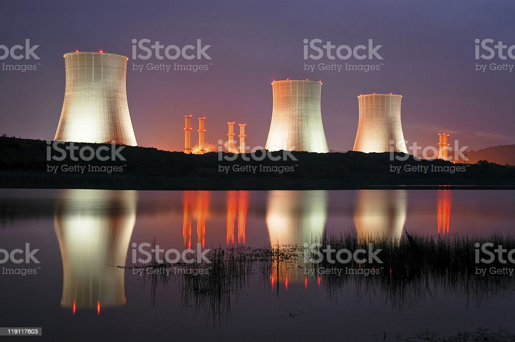The towers of a power station lit up at night  stock photo