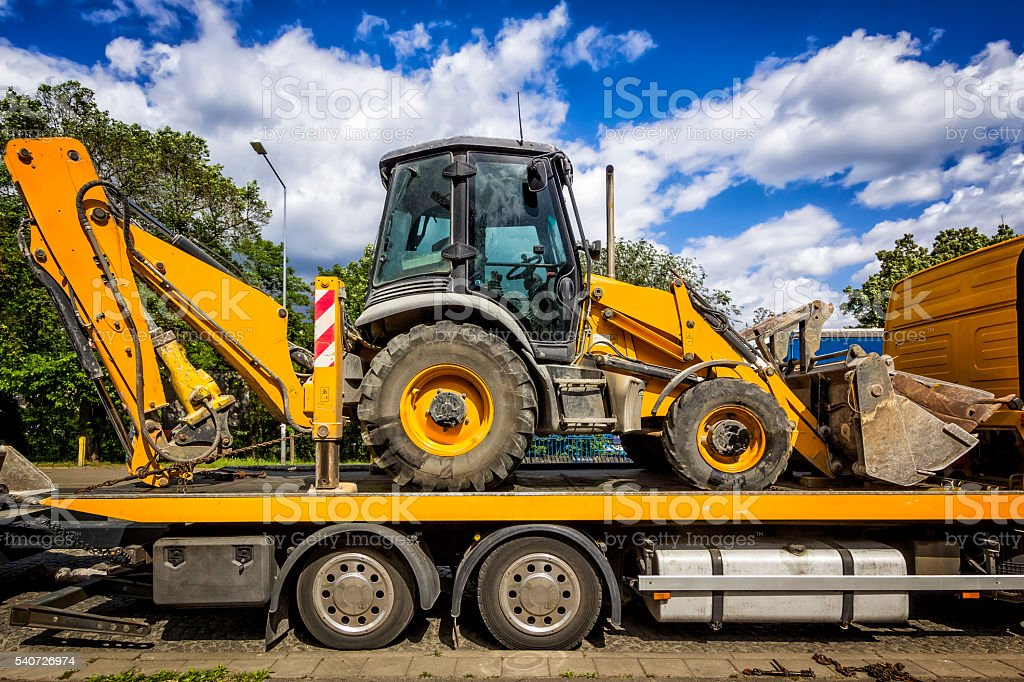 The trailer platform with yellow Backhoe stock photo
