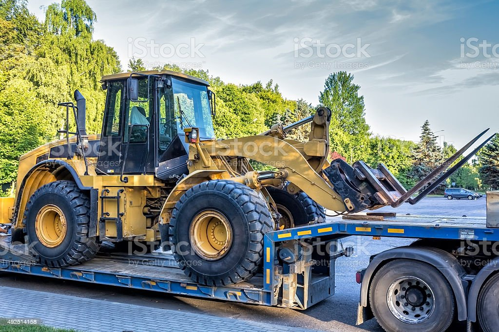 The trailer platform with yellow earth mover stock photo