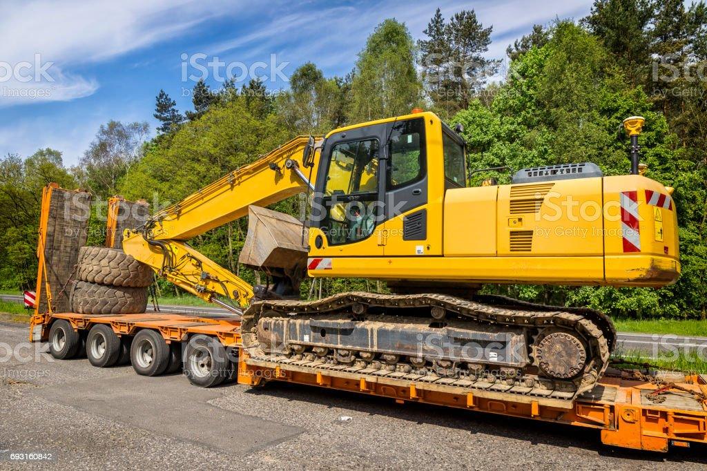 The trailer platform with yellow excavator stock photo