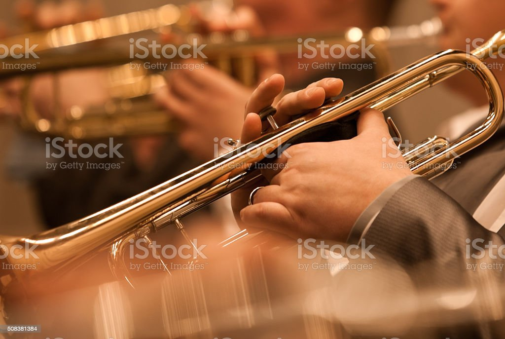 The trumpet in the hands of a musician in the orchestra stock photo