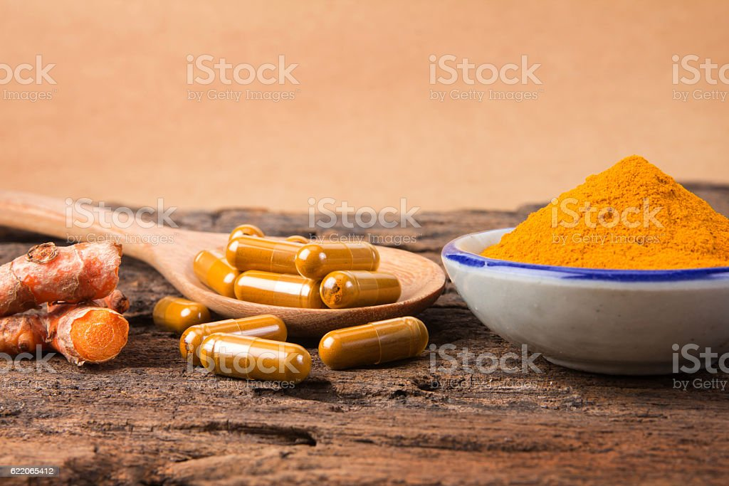 the turmeric powder and capsule and roots curcumin stock photo