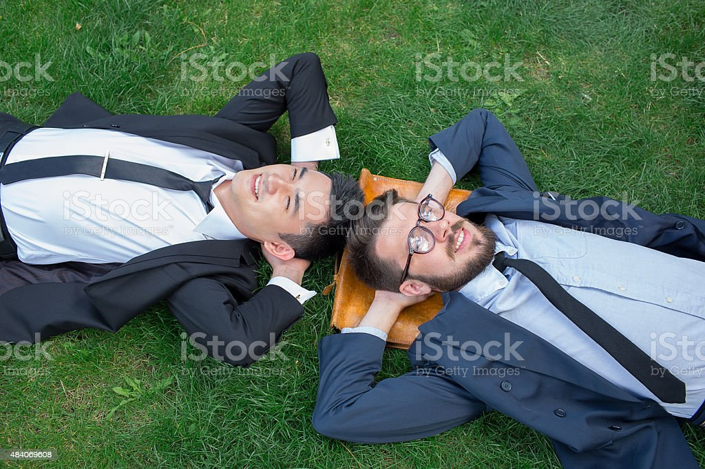 The two happy young businessmen in a suit lying on stock photo