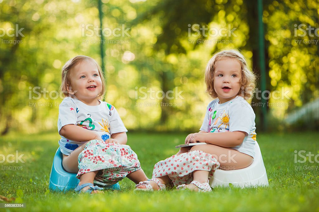 The two little baby girls sitting on pots stock photo