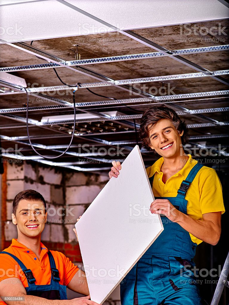 The two men set a false ceiling stock photo